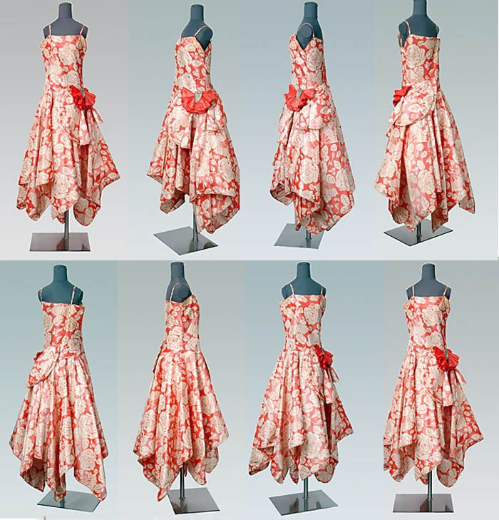 """Evening dress, Lanvin, 1929. Silk taffeta ikat-weave dress in red and white floral pattern. Simple camisole bodice has lowered waistline; circular skirt has handkerchief (rectangular) hemline. Bodice & skirt are assymetrical. At dropped waist on left side, layered semi-circular pieces held by heavy rhinestone- & crystal-decorated rectangle of fabric, form """"bow""""-shape. Hem of skirt bound with narrow bias. Drexel Univ."""