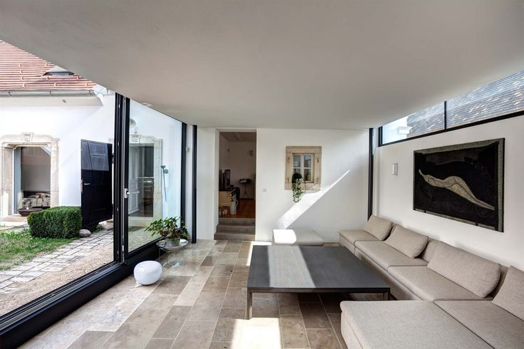 Kontrastní kompozici změkčují přírodní odstíny kamenných podlah a nábytku, který si vybírali majitelé sami. Rádi se také obklopují uměním.