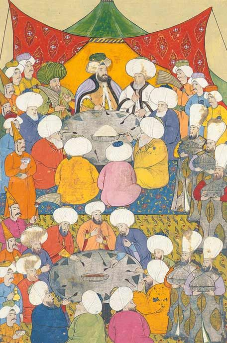 """Bankett für Würdenträger Beim Festmahl mit dem Sultan sind geistliche Würdenträger, die Angehörigen der Ulema, versammelt. Mit langstieligen Löffeln essen sie gemeinsam aus den Schüsseln, während Diener weitere Speisen auftragen. Levni, osmanische Miniaturmalerei, aus dem """"Surname-ı Sultan Ahmed Han"""", ca. 1720."""