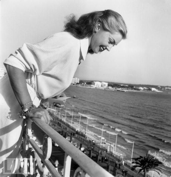 *Esther Williams Stays Dry  Esther Williams, famous for her swimming movies, throws autographs off a balcony to her fans during the Cannes Film Festival on April 27, 1955.