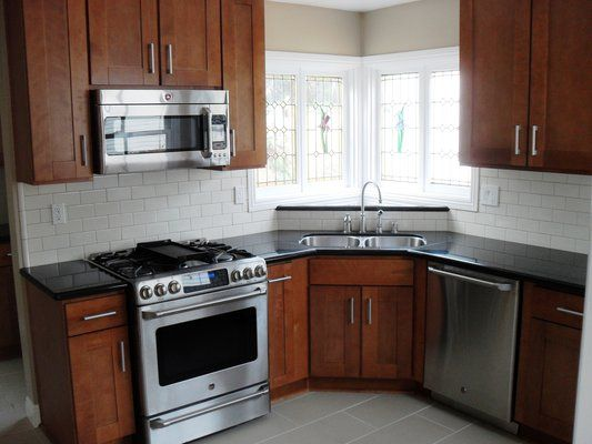 Medium wood cabinets white subway tile blacksplash for Are white kitchen cabinets still in style