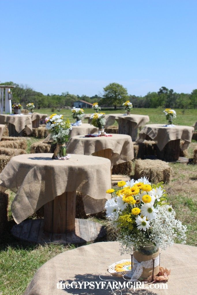 Mason jar centerpieces at a vintage farm wedding. Wooden spools were covered with burlap tableclothes and guest sat on hay bales.