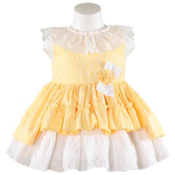 Miranda Textilesin kaunis keltainen mekko. Pääntiellä pitsi, vyötäröllä valkoinen rusetti ja helmasta jää näkyviin mekon valkoinen pitsialuskerros. Lisäksi selkäpuolella on keltainen rusetti. www.nellikki.fi