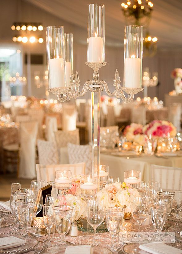 The reception was held in a blush and cream filled tent, which was bathed in a romantic glow from chandeliers overhead and tables covered in candlelight. #WeddingCenterpieces