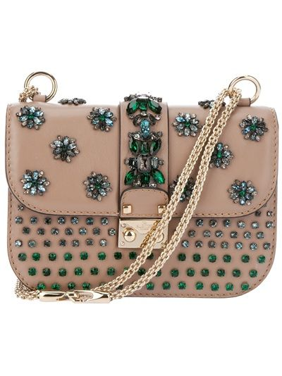 Pale brown clutch from Valentino featuring a flap design with green flower jewel embellishments, a gold-.tone lock with an embossed logo, white and green square jewel embellishments and two gold-tone chain handles. The interior features a zip pocket and a leather logo patch.