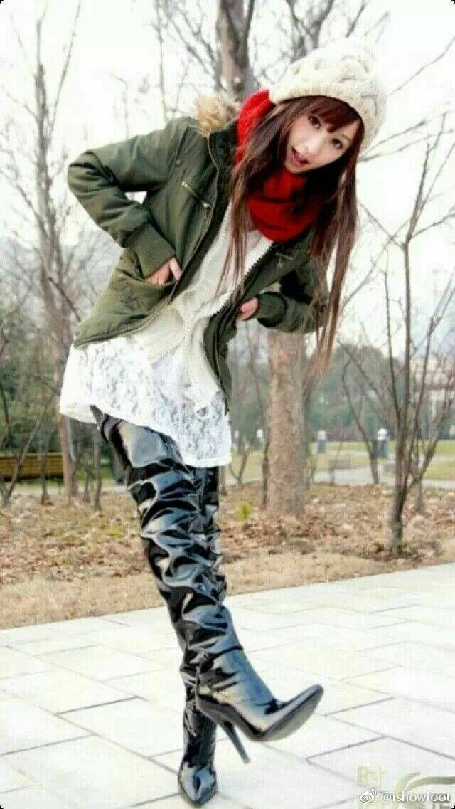 Asian girl in black patent leather slouchy thigh boots