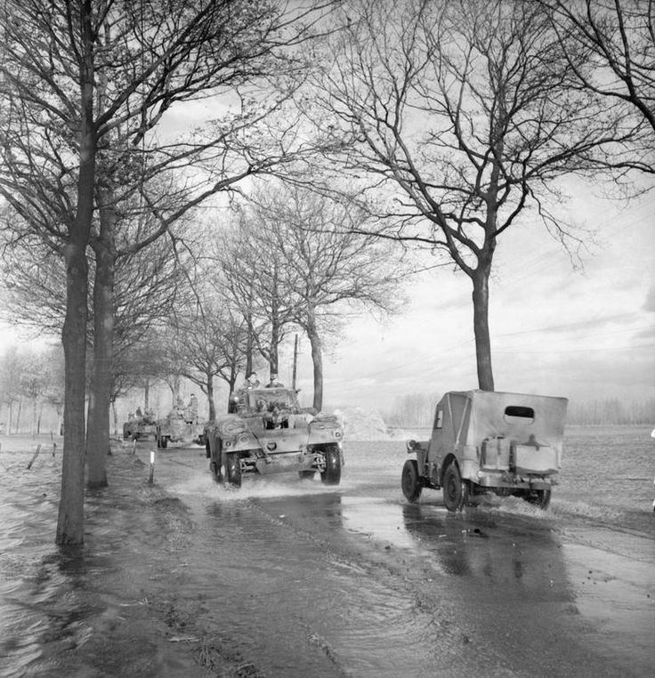 Daimler armoured cars and a jeep negotiate a flooded road in Holland, 26 November 1944.