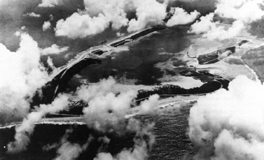 A May 1941 photo taken from the northeast, from a Navy Catalina flying boat, reveals the Wake Island coral atoll in the mid-Pacific beneath broken clouds. Wishbone-shaped Wake proper lies at left, as yet unmarked by construction of the airfield there. The upper portion of the photo shows Wilkes; at right is Peale, joined to Wake by a causeway.