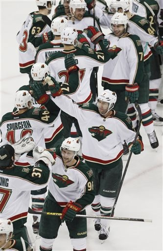 From bottom to top on right, Minnesota Wild left wing Pierre-Marc Bouchard, center Matt Cullen and defenseman Tom Gilbert celebrate with teammates after the Wild's 3-1 victory over the Colorado Avalanche in an NHL hockey game in Denver on Saturday, April 27, 2013. With the win, the Wild earned the eighth seed in the NHL Western Conference playoffs. (AP Photo/David Zalubowski)