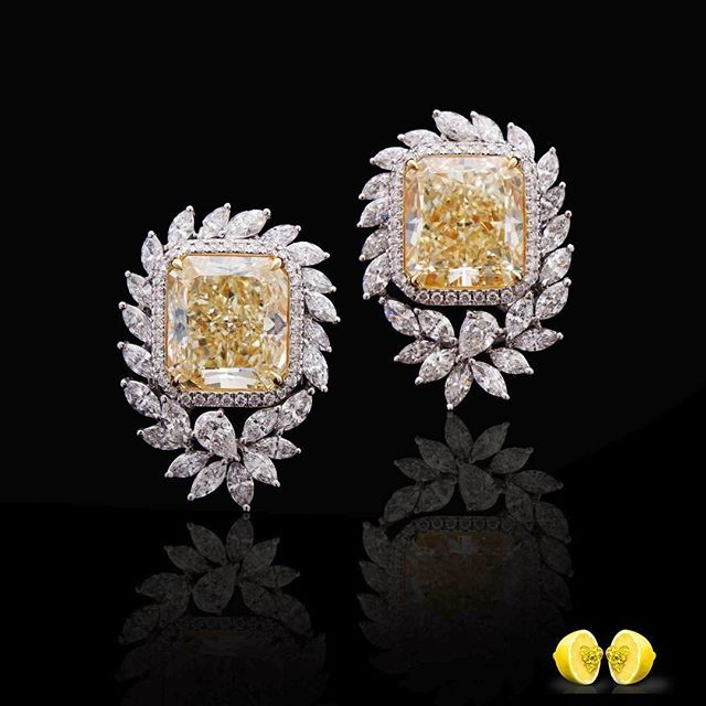 A magnificent pair of earrings - fancy yellow cushion diamonds, halo setting, with colorless Marquise and a single pear shape diamond.