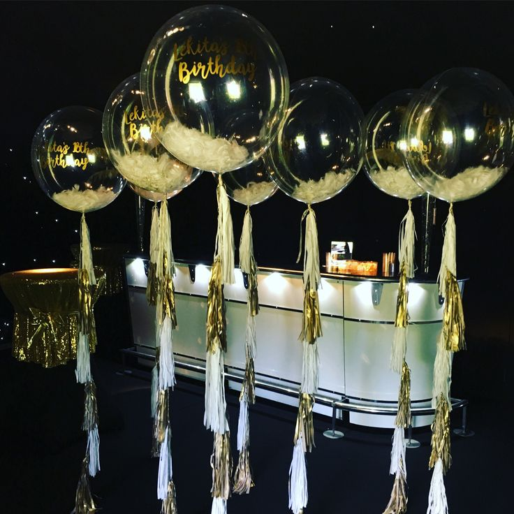 White feather and gold glitter filled 24inch clear balloons attached to white and gold tassel tails for a glam LA night party