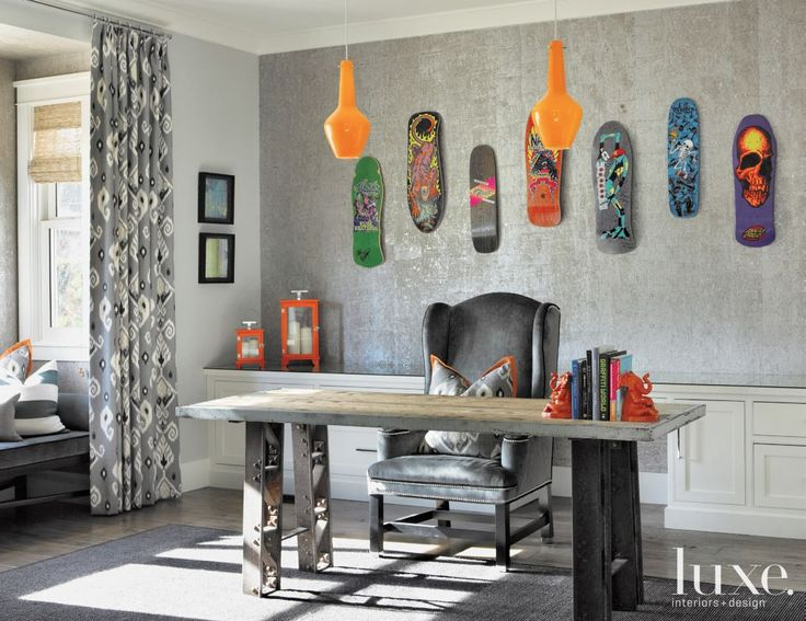 A faux-cork wallcovering backs the owners' collection of skateboard decks in the study. A vintage German industrial table works as a desk, and the custom wing chair and drapery fabric are from Barclay Butera.