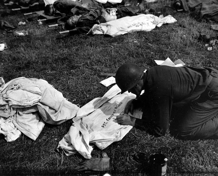 """GI ,a member of a Graves Registration Company wrote, kneeling on a canvas to serve as a """"body bag"""" for the body (including major rows seen in stretchers behind) the name of the slain: PFC Frederick R Smith.  In the US Army, it is said that the body must be placed in a """"Shroud"""" (a shroud) or """"wrapped"""" (packed) """"wrapped"""" in a mattress cover, a blanket, half tent, a poncho. ... and closed by pins to nurses.  The paratroopers were buried in a parachute."""