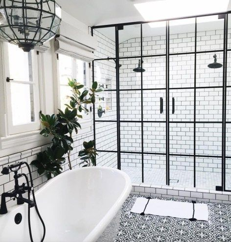 Bathroom with black hardware, black framed shower doors, black and white…