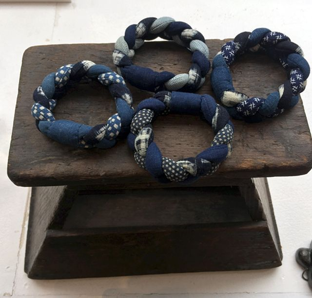 THE MAGIC FINGERS OF REIKO OKUNUSHI   Okunushi san can make anything:  jewelry, pins, and charming necklaces of old leftover indigo fabric. She recycles old fabrics and gives them new life. She throws nothing away. These flexible braided bracelets of old indigo are always popular    Blue & White, Tokyo