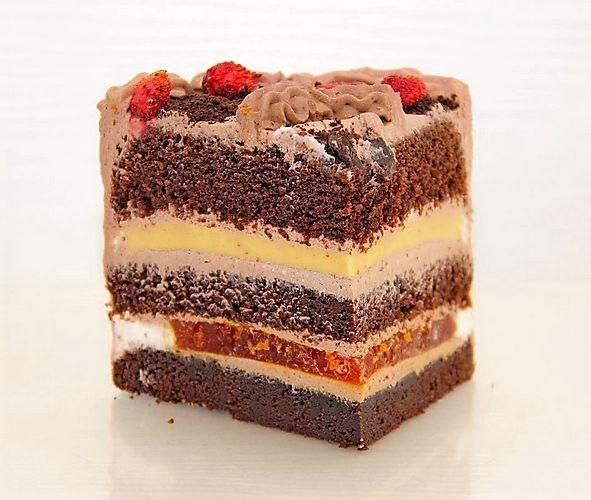 Сочный шоколадный бисквит, апельсиновое желе, апельсиновый конфи с лёгкой пряной ноткой, шоколадный мусс, сливочная карамель и орехи.