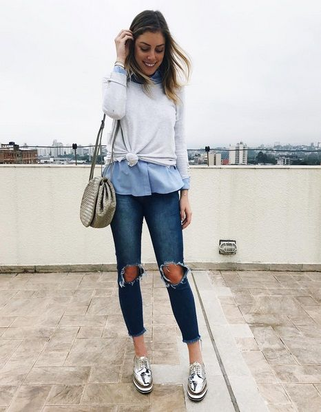 Sobreposição de malha com nózinho e camisa azul, calça jeans rasgada no joelho e sapato metalizado