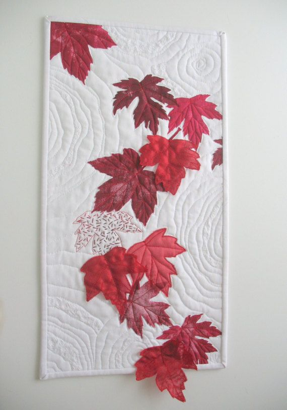 Canada 150 Art Quilt. Red maple leaves have been hand painted onto white cotton. Free motion machine quilting and hand stitching in a circular pattern add movement to the drifting leaves. Three additional handmade organza leaves are stitched to the top so that they seem to be floating right off the surface.  This art quilt is my original design and has been created using locally gathered maples leaves to make the stencils that I used when painting the leaves. The organza leaves have been…