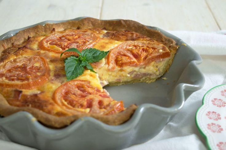 ΥΛΙΚΑ  Για την βάση( 35 εκ. ):  90 ml ελαιόλαδο 1 αυγό, σε θερμοκρασία δωματίου 90 ml γάλα, σε θερμοκρασία δωματίου 1 πρέζα αλάτι 1 κ. γ μπέικιν πάουντερ 300 γρ. περίπου αλεύρι, για όλες τις χρήσεις Για τη γέμιση:  140 γρ. τυρί έμενταλ, τριμμένο 140 γρ. τυρί κασέρι, τριμμένο 140 γρ. τυρί γκούντα, τριμμένο 3 φέτες μπέικον, κομμένο σε κυβάκια 5 φέτες ζαμπόν, κομμένο σε κυβάκια 2 αυγά 250 ml κρέμα γάλακτος 4 ροδέλες ντομάτας, λεπτά κομμένες