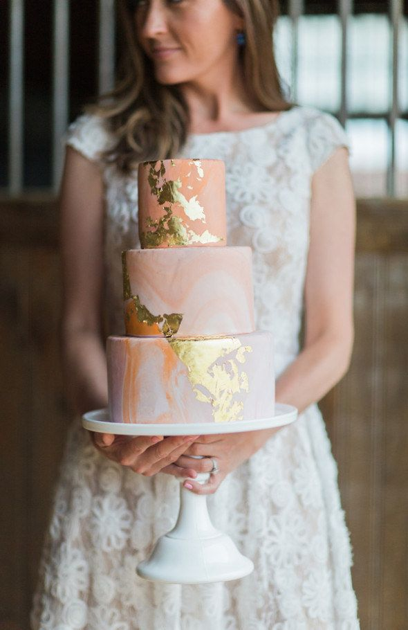 A pretty, peach-colored cake with gold accents.