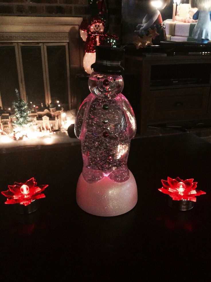 Multi-color snowman with red tea lights next to it