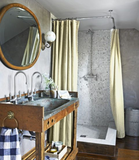 Antique sconces, canvas shower curtains, and a vintage copper sink basin bring a sense of history to the master bathroom in this New York farmhouse.