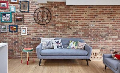 grey sofa exposed brick wall in a kitchen diner
