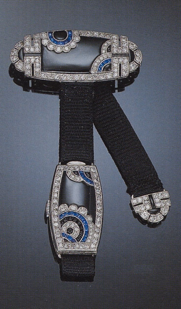 An Art Deco diamond and gem set lapel watch. The lozenge shaped brooch with floral geometric patterning of diamonds and buff-top sapphires atop a black onyx ground to the black ribbon suspending a lozenge shaped watch of similar design, opening to reveal a cream coloured dial with Arabic chapters, with French assay marks. Source: Christie's catalogue, Sale 9400, Important Jewelry, 29 March 2000, Los Angeles.