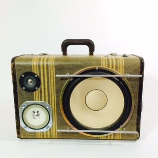 """Model: DELUXE   Year: 1940's  Weight:14-lbs  Dimensions: 18x7x13  Specifications: 200watt Amplifier15+hr RECHARGEABLE lithium-ion battery life 10"""" White wall subwoofer with mid-range & tweeter   Aluminium Jail-Bars  1960's Chrome Volkswagen Ashtray   Aux input for easy plug in to any mobile device  Vintage tweed guitar strap (comes on and off very easily)  Custom hand built interior using vintage plaid  Volume, Bass & Treble knobs     """"Koch's Original Aviation Luggage"""" Turned up ..."""