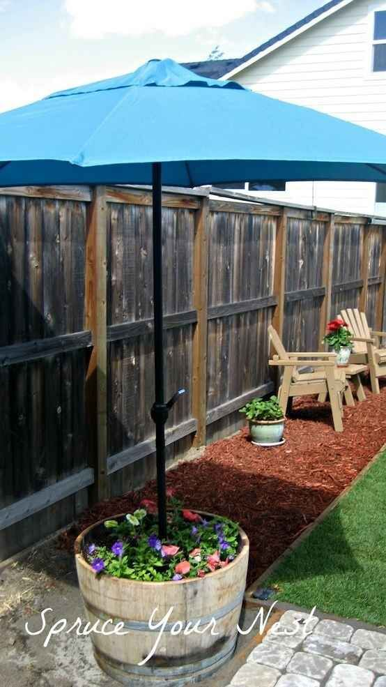 Make a garden umbrella stand using a pot or a barrel. | 51 Budget Backyard DIYs That Are Borderline Genius