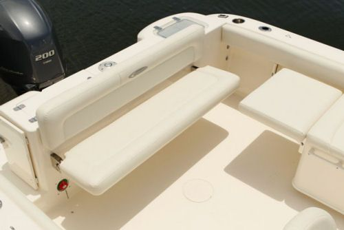 Cobia 220 Dual Console: The fold-away transom bench seat is standard on the 220 Dual Console, and it together with the extended convertible chaise seat seen at the right offers cruising and sunning functionality. Not that the transom door (left) opens out, which we like to see on small offshore boats.