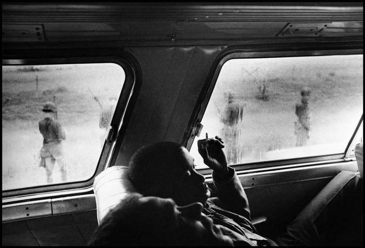 """Bruce Davidson - Un """"Freedom Rider"""" (un attivista del movimento per i diritti civili dei neri che si oppone alla segregazione razziale sugli autobus) durante l'occupazione di un autobus in Alabama, mentre all'esterno sono schierati i soldati della Guardia Nazionale, Alabama, Stati Uniti 1961"""