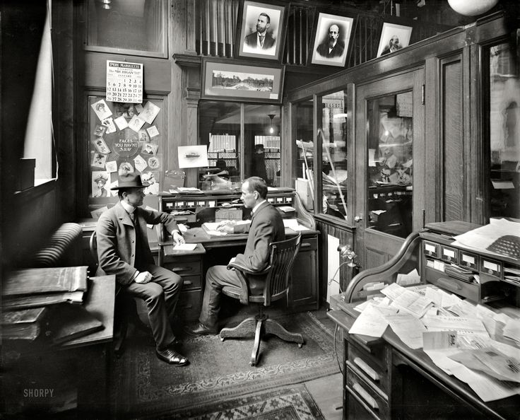 "Office Visit: Detroit, Michigan. January 1902. ""Richmond & Backus Co. office."" A peek behind the scenes at R&B -- printers, binders and ""office outfitters"" -- reveals a cozily cluttered workspace enlivened by a display of ""faces you hav'nt saw."" 8x10 inch dry plate glass negative, Detroit Publishing Company. Click to view full size."