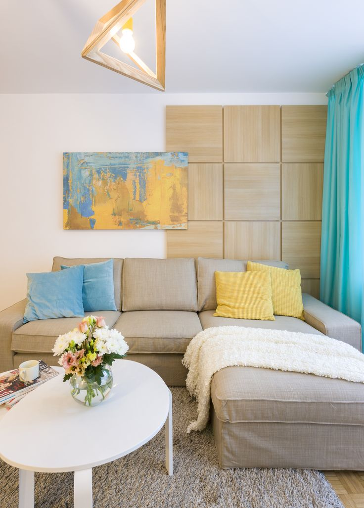 Cosy grey sofa with colored pillows and a customized canvas print, wood accents. Turquoise accents  and a vintage floor.