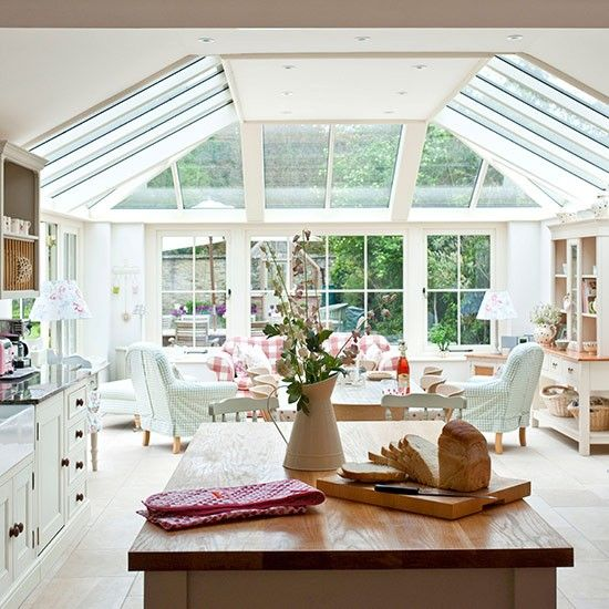 Open-plan kitchen with window wall, neutral flooring, white cabinetry and wooden worktop
