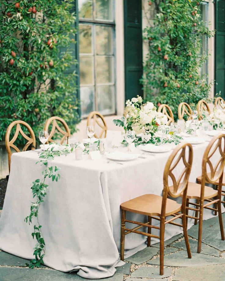 An Intimate Garden Wedding at a Michigan Bed & Breakfast | Martha Stewart Weddings - For an elegant wedding reception, tables were decorated with loose-form blooms and trailing smilax greenery. Cream-colored linens, candles, and handmade Italian ceramic lace-style chargers completed the table decor, and wooden chairs catered to the neutral wedding color palette. #weddingideas #wedding #weddingflowers #gardenwedding