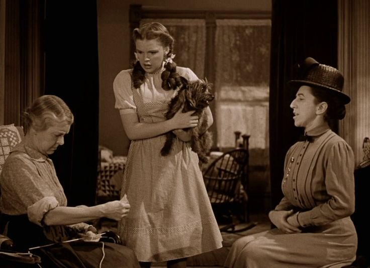 The Wizard of Oz (1939) - Almira Gulch comes to talk to Dorothy's uncle and Aunt Em (Clara Blandick), who is knitting here, about Dorothy's dog, Toto.