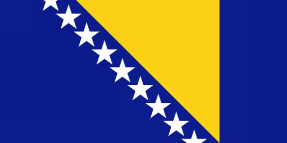 The Bosnia-Herzegovina flag, adopted February 4, 1998, has a blue background with a yellow inverted triangle in the center. To the left of the triangle is a row of white stars in a line from the top edge to the bottom edge of the flag.