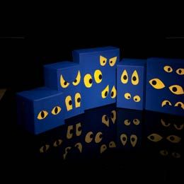"""FamilyFun's """"spectral eyes"""": paint boxes midnight blue; cut holes; cover holes with yellow tissue paper; put a wire of fairy lights through (no bulbs outside the boxes) ... Maybe make luminaries like this that spell out Happy Birthday???"""