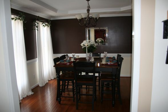 Chocolate brown dining room with white trim provides a perfect