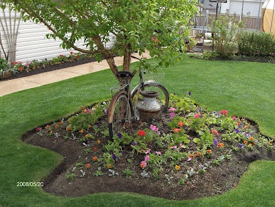 Different shaped flower bed with old bicycle and milk can for Flower bed shapes designs