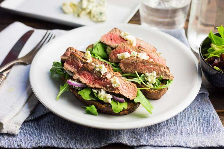 Recept voor biefstuk sandwich voor 4 personen. Met zout, boter, olijfolie, aluminiumfolie, biefstuk, blauwe kaas, bruin brood, slamelange, rode ui en knoflook