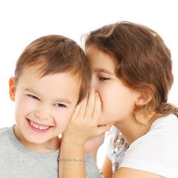 A picture of a little girl telling a secret to her brother over white background
