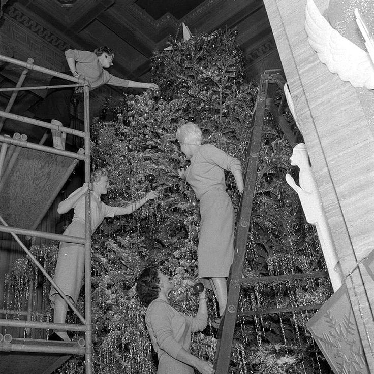 Four ladies on scaffolding and ladders decorating Christmas tree in the Southern California Edison General Office lobby, 1957