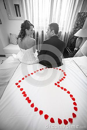 Newlyweds in bedroom with red petals heart. Black and white