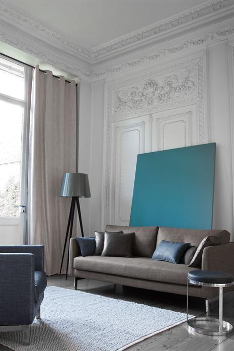 Salon classique avec moulures décorative et mobilier contemporain.