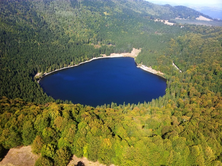 """Lake Sfânta Ana, Transylvania, Romania. Lake Sfânta Ana is the only crater lake in Romania located in the volcanic crater named """"Puciosul"""" of the Eastern Carpathians, near Tuşnad in the Natural Reserve of Mohoș, Harghita County, Romania."""