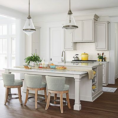 Define Your Space Interior designer Ginger Brewton hung oversize pendants from Circa Lighting above the island to help delineate the kitc...