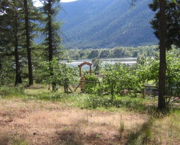A waterfront and mountain view of a country house and property for sale in the Cariboo region of BC Canada.
