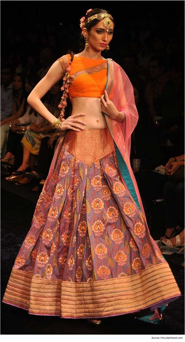 A boatneck lehenga blouse design with mega sleeves in orange and lace work in pastel colour is paired with a pink tissue #dupatta with silk blue and golden border and printed brocade #lehenga, this garment is sleek and elegant for a sangeet and #mehendi function.
